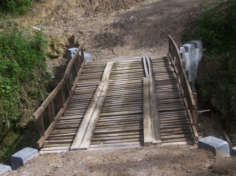 Terlihat dalam Gambar Jembatan Mbergang-Lae Leam hanya terbuat dari kayu, sementara menurut informasi seharusnya dikerjakan dengan menggunakan plat beton. @