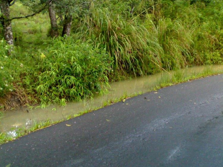 Setiap kali hujan turun parit alam yang terdapat pada jalan ini berubah fungsi menjadi penampungan air. Sementara jika debit air semakin besar, air meluap dari badan jalan yang telah mengakibatkan kerusakan pada bahu jalan pada bagian seberang penampungan. @